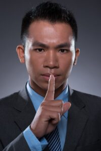 Vertical portrait of a young businessman making a hush