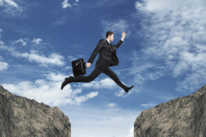 Business man jumping from one cliff to another
