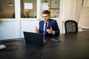 Business man sitting in front of a computer, speaking to a potential customer, trying to build rapport.