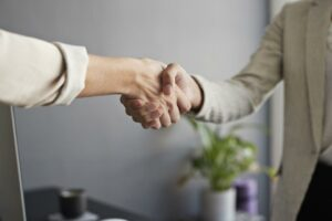 Sales rep shaking hands, accepting a sales manager position